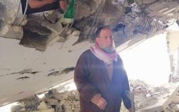 صورة والدة الشهيد صالح البرغوثي يقف على انقاض منزله المدمر