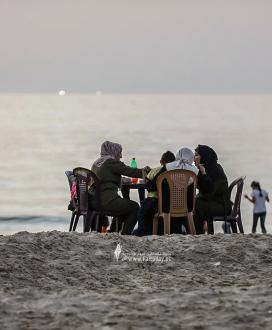 عائلات فلسطينية تتناول طعام الإفطار الرمضاني على شاطئ بحر غزة، بعد إلغاء حظر التجول.